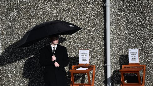 An undertaker stands beside a book of condolence outside the church. Photograph: Charles McQuillan/Getty Images