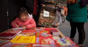 """Three hours a day, those Chinese kids get, twice the global homework average."" A girl as doing her homework on a street in Chengdu, Sichuan province. Photograph: Ed Jones/AFP/Getty Images"