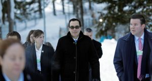 Steven Mnuchin, the US treasury secretary, walks through the snow during at Davos. Mr Mnuchin said he isn't concerned about short-term fluctuations in the dollar, a day after he suggested a weaker US currency would help trade. Photograph: Markus Schreiber / AP Photo