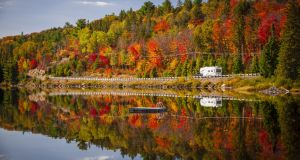Fall forest with colorful autumn leaves and highway 60 reflecting in Lake of Two Rivers. Algonquin Park, Ontario, Canada