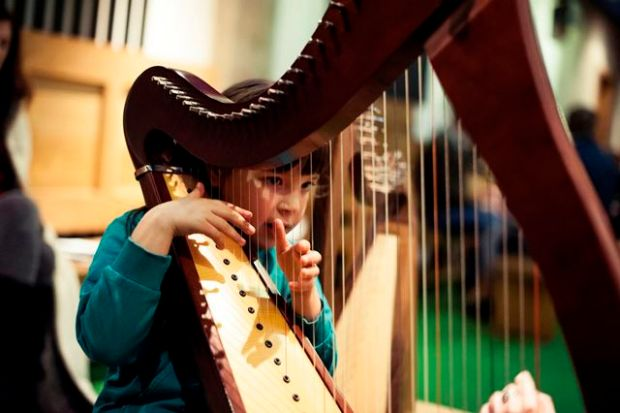 A girl plays harp as part of Tradfest in Dublin