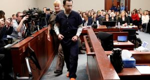 Larry Nassar, a former team USA Gymnastics doctor who pleaded guilty to sexual assault charges, is escorted into the courtroom during his sentencing hearing in  Michigan, US, on Wednesday. Photograph: Brendan McDermid/Reuters