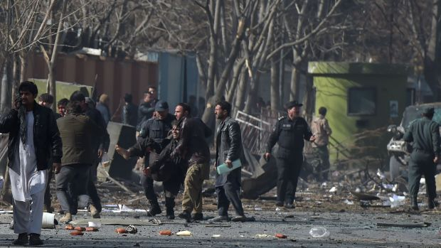 Afghan volunteers and policemen help the wounded at the scene of a car bomb in Kabul. Photograph: AFP