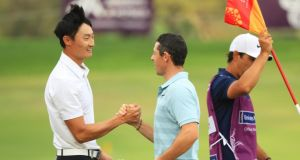 Rory McIlroy congratulates Haotong Li after his victory in Dubai. Photograph: Andrew Redington/Getty