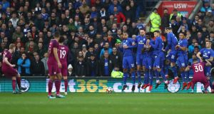 Kevin De Bruyne sends his free kick under the wall against Cardiff city. Photograph: Michael Steele/Getty