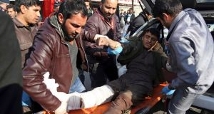An injured man is moved to a stretcher outside a hospital following the suicide attack in Kabul, Afghanistan, on  January  27th. Photograph: AP Photo/Rahmat Gul