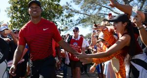 Tiger Woods with a fan on the final day of the Farmers Insurance Open. Photograph: Donald Miralle/Getty