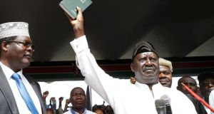 Kenyan opposition leader Raila Odinga holds a Bible as he takes a symbolic presidential oath of office in Nairobi on Tuesday. Photograph: Baz Ratner/Reuters