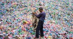 A Chinese labourer sorts plastic bottles for recycling in Dong Xiao Kou village, on the outskirts of Beijing. Photograph: Fred Dufour/AFP/Getty Images