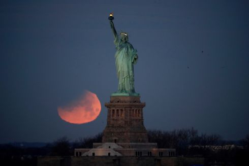 SUPER BLUE BLOOD MOON: The Statue of Liberty is backdropped by a supermoon, as seen from the Brooklyn borough of New York. The supermoon, the last of three consecutive supermoons,  experienced lunar eclipse as it set, but only a partial eclipse was visible in the east US coast. Photograph: Julio Cortez/AP Photo