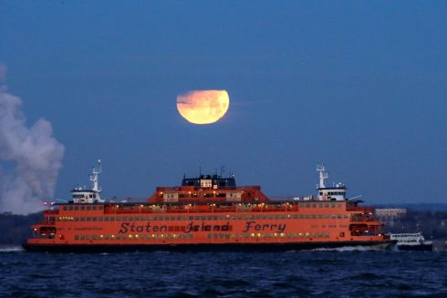 STATEN ISLAND: The Super Blue Blood Moon sets behind the Staten Island Ferry, seen from Brooklyn, New York, US. Photograph: Eduardo Munoz/Reuters