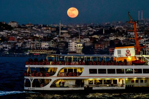 BOSPHORUS STRAITS: A boat sails on the Bosphorus Straits in Istanbul, Turkey, as the supermoon hovers in the background.  Photograph: Yasin Akgul/AFP/Getty Images