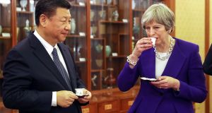 British prime minister Theresa May drinks next to Xi Jinping, China's president, during a tea ceremony at the Diaoyutai state guesthouse in Beijing on Thursday. Photograph: Dan Kitwood/EPA