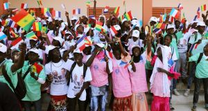 Children wave flags  during the inauguration of the Bel-Air secondary school in Dakar, Senegal, at the same time as a conference organised by the Global Partnership for Education. Photograph: Ludovic Marin/AFP/Getty Images
