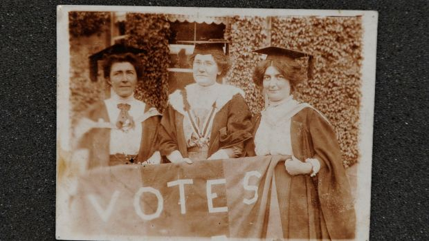 "From left - Hanna Sheehy-Skeffington, Kathleen Shannon and Kate Sheedy, in their graduation robes and mortar-boards, carrying a banner saying ""Votes"" (for women)"