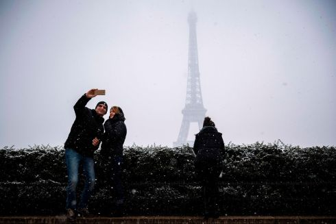 SNOWY SELFIE: A couple pose for a selfie under snow on the Place du Trocadero in front the Eiffel Tower in Paris. Photograph: Lionel Bonaventure/AFP/Getty Images