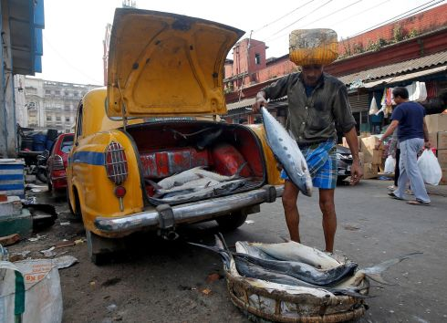 FISHY FARE: A worker unloads fish from the boot of a taxi at a fish market in Kolkata, India. Photograph: Rupak De Chowdhuri/Reuters
