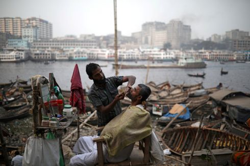 STREET SALON: A man has his beard groomed at a street salon at the bank of the Buriganga river in Dhaka, Bangladesh. Photograph: Mohammad Ponir Hossain/Reuters