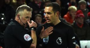 Referee Jon Moss discusses the first penalty with  linesman Edward Smith during the  Premier League  match between Liverpool and Tottenham. Photograph:    Paul Ellis/AFP/Getty Images
