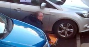 Sinn Fein MLA Gerry Kelly removes a clamp  from his car