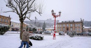 A man walks on a street covered with snow in Montmedy, north of France. Photograph: EPA/Julien Warnand