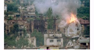 A house near the Jewish cemetery in  Sarajevo  burns after being hit by a mortar shell in September 1994. Photograph: Peter Andrews / Reuters