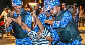 Maldivian police officers detain an opposition protester demanding the release of political prisoners during a protest in Male last Friday. Photograph:  Mohamed Sharuhaan/AP