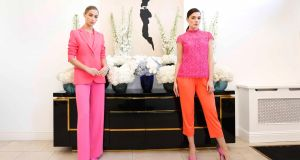 Thalia (L) wearing Coco Crepe Coral Jacket (€995), Abby Silk Coral Top (€495), Rachel Crepe Fuchsia Trousers (€495) and Kelly wearing Adele Lace Fuchsia Top (€795), Yoshi Coral Jersey Trousers (€495). Photograph: Sasko Lazarov / Photocall Ireland