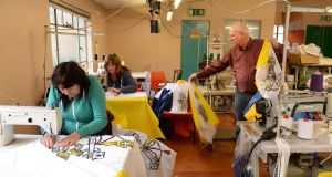 Ken Cairns and Marion Redmond at Prospect Design Flag Manufacturers prepare yellow and white papal flags at the factory in Montague Lane. Photograph: Dara Mac Dónaill