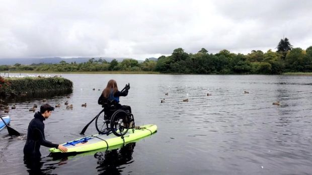 Geraldine Lavelle paddleboarding in her chair: she uses a manual, rather that a power wheelchair, in order to maintain her fitness levels
