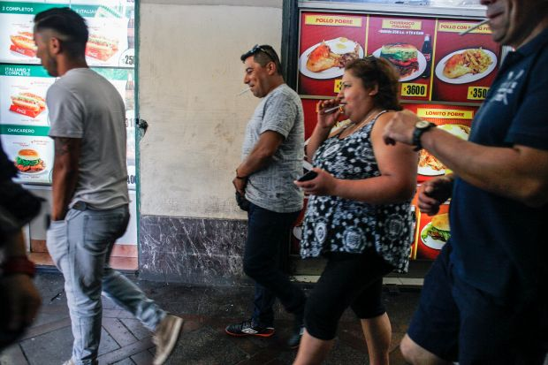 Passers-by in front of a fast food restaurant in downtown Santiago. The medical cost of obesity was 2.4 percent of all health care spending in Chile in 2016 and could rise to 4 percent by 2030.