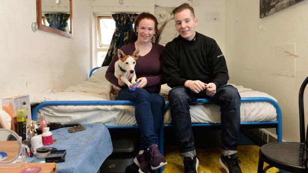 Mary and Paulie with their dog Scooter, at their accommodation. Photograph: Dara Mac Dónaill/The Irish Times