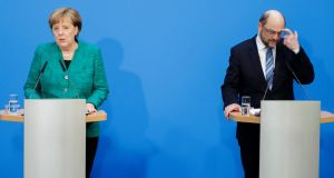 To win over the Social Democrats and secure a fourth term as chancellor, Angela Merkel has surrendered to the key finance, foreign and labour portfolios to the SPD, led by Martin Schulz. Photograph: Carsten Koall/Getty Images