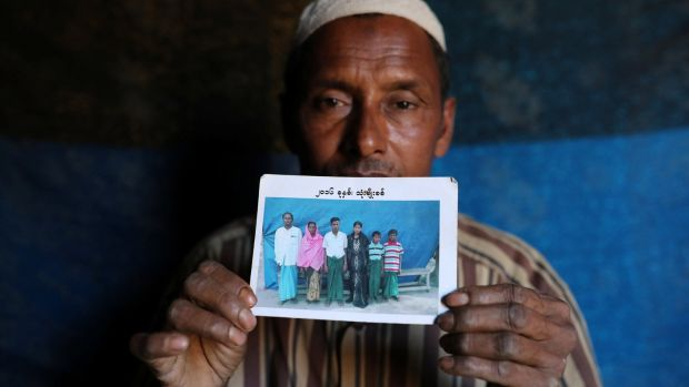 Abdu Shakur, whose son Rashid Ahmed was among 10 Rohingya men killed by Myanmar security forces and Buddhist villagers on September 2nd, holding a family photograph at Kutupalong camp in Cox's Bazar, Bangladesh. Photograph: Mohammad Ponir Hossain/Reuters