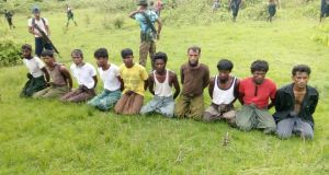 Ten Rohingya Muslim men with their hands bound kneel as members of the Myanmar security forces stand guard in Inn Din village on September 2nd. The men were then executed and their bodies thrown into a mass grave, a Reuters investigation showed. Photograph: Reuters