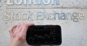 A view of the Stocks app on an iPhone against the London Stock Exchange sign in the City of London. Photograph: Kirsty O'Connor/PA Wire