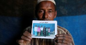 Abdu Shakur, whose son Rashid Ahmed was among 10 Rohingya men killed by Myanmar security forces and Buddhist villagers on September 2nd, 2017, holds a family picture at Kutupalong camp in Cox's Bazar, Bangladesh. Photograph: Mohammad Ponir Hossain/Reuters