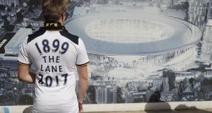 A Spurs fan looks at an artist's impression of the new stadium