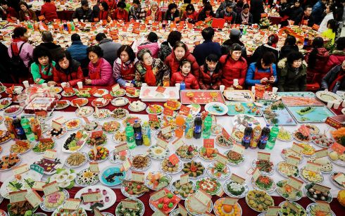 CHOW DOWN: Neighbourhood residents sit around a table laden with homemade dishes in Wuhan, Hubei province, China, marking the 23rd and 24th days of the 12th month of the Chinese lunar year. Photograph: Wang He/Getty Images