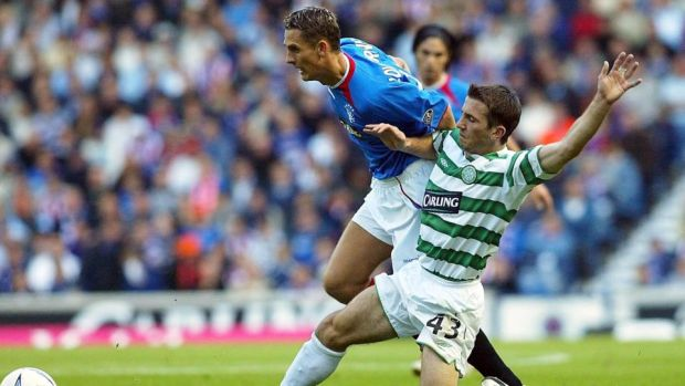 Liam Miller tackles Peter Lovenkrands durinf an Old Firm derby in 2003. Photograph: Inpho