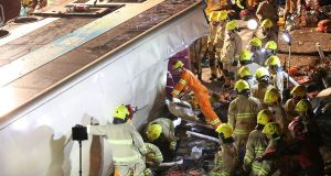Firefighters and emergency personnel work at the site of a fatal  incident after a double-decker bus  crashed and toppled over  near the town of Tai Po in Hong Kong's northern New Territories. At least 19 people are reported to have been killed and dozens injured. Photograph: AFP/Getty Images