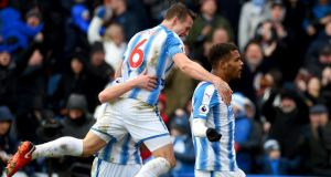 Steve Mounie of Huddersfield Town celebrates with teammate Jonathan Hogg after scoring his side's third goal during their Premier League win over Bournemouth. Photo: Tony Marshall/Getty Images