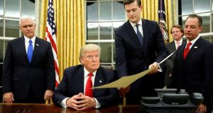 A file image from last month of former White House staff secretary Rob Porter (second right) gives Donald Trump, flanked by vice president Mike Pence (left) and chief of staff Reince Priebus (right), the document. Photograph: Reuters