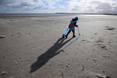SCOUTING FOR RUBBISH: The 66th Naomh Eoin Cub Scouts, based in Clontarf, clean up litter on Dollymount Strand. Above, a wind-swept Emily Yeates (9) picks up rubbish which will be transformed into musical instruments as part of Dublin's Culture Connects: The National Neighbourhood, a Dublin City Council initiative. Photograph: Mark Stedman