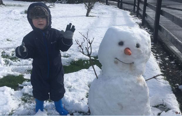Three-year-old Gavin Bohan from Galbally Road with the first snowman he has built.