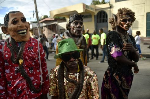 "HAPPY HAITIANS: Revellers garlanded with snakes perform on the first day of the 2018 National Carnival Parade in Port-au-Prince, Haiti. The name of the carnival for this year in Haitian creole is ""Ayiti sou wout chanjman"" (Haiti on the road to change). Photograph: Hector Retamal/AFP/Getty Images"
