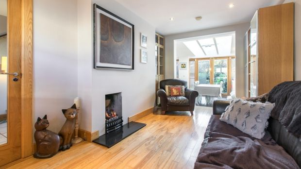 The long livingroom has a solid oak floor and a small coal-effect gas fire