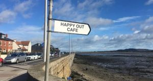 A simple black and white sign pointing out to sea: The Happy Out Cafe on Dollymount Strand