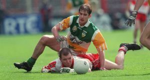 Derry's Johnny McBride  is tackled by Offaly's Colm Quinn during the National Football League final of 1998. Photograph: Patrick Bolger/Inpho