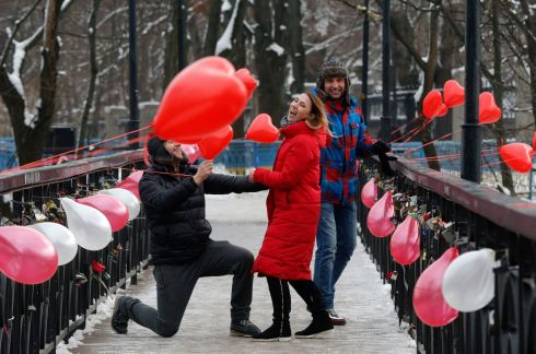 BE MINE: A man gestures to a woman as he kneels in front of her on the Bridge of Love in Kiev, Ukraine, on St Valentine's Day. Photograph: Efrem Lukatsky/AP Photo